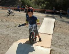 A toddler on a push bike rides the ramp at Take a Kid Mountain Biking Day